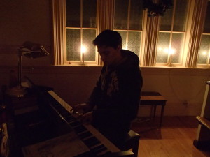 Savage practices on the church piano by candlelight!