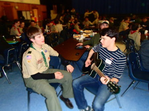 Savage plays music while chatting with Dylan Bunker from Troop 201 at the Merit Badge College.